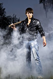 Handsome man with chainsaw. And abstract smoke stock photo