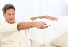Handsome man changing channel Royalty Free Stock Photos