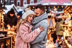 A handsome man and charming girl cuddling and enjoying spending time together while standing at the winter fair at a. An attractive couple in love, a handsome royalty free stock images