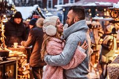 A handsome man and charming girl cuddling and enjoying spending time together while standing at the winter fair at a royalty free stock image