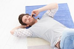 Handsome man chatting on mobile smiling. Handsome young man laying on floor in living room, chatting on mobile phone, smiling royalty free stock photos