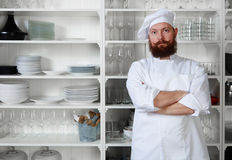 Handsome man chef standing with his arms crossed against a white cabinet with dishes Royalty Free Stock Photo