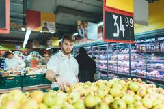 A handsome man chooses apples in a supermarket. The family man buys fruit in the store. Shopping in a supermarket. stock photos