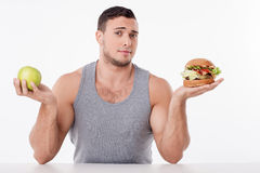 Handsome man chooses between healthy and unhealthy Stock Images