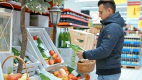 Handsome Man is Choosing Apple Cider in the Supermarket. Near Beautiful Autumn Stand with Apples and Drinks stock video