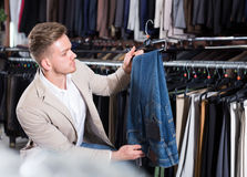 Handsome man choosing new trousers Stock Photo