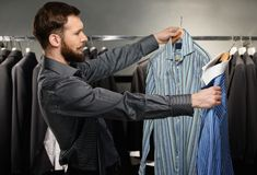 Handsome man choosing shirt Stock Image