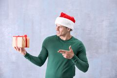 Handsome man in Christmas hat holding gift box. Handsome man in Christmas hat  holding gift box on color background Stock Images