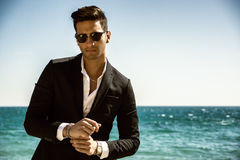 Handsome man in classical suit on beach. Young handsome man in classical suit on beach holding sunglasses while looking away. Sea waves on background Stock Image