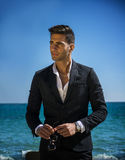 Handsome man in classical suit on beach. Young handsome man in classical suit on beach holding sunglasses while looking away. Sea waves on background Stock Images