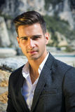 Handsome man in classical suit on beach. Young handsome man in classical suit on beach holding sunglasses while looking away. Sea waves on background Stock Photography