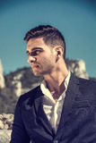 Handsome man in classical suit on beach. Young handsome man in classical suit on beach holding sunglasses while looking away. Sea waves on background Stock Photos