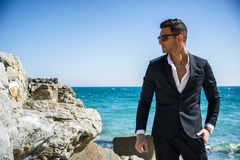 Handsome man in classical suit on beach. Young handsome man in classical suit on beach holding sunglasses while looking away. Sea waves on background Stock Photo