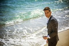 Handsome man in classical suit on beach Stock Images