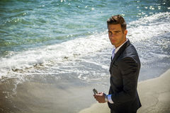 Handsome man in classical suit on beach. Young handsome man in classical suit on beach holding sunglasses while looking at camera. Sea waves on background Royalty Free Stock Photography