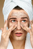 Handsome man cleans face scrub on skin. Stock Image