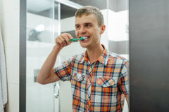 Handsome man cleans teeth  in the bathroom and smiling Royalty Free Stock Image