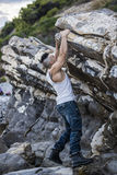 Handsome Man Climbing a Rock at the River Stock Photo