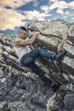 Handsome Man Climbing a Rock at the River Royalty Free Stock Photos