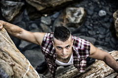 Handsome Man Climbing a Rock at the River Royalty Free Stock Image