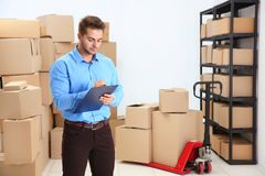 Handsome man with clipboard in logistics company. Warehouse Royalty Free Stock Photography