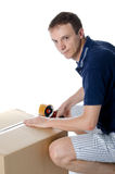 Handsome man closing cardboard box with adhesive tape Stock Photos