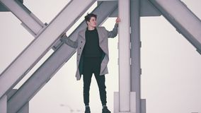 Handsome man in coat standing under the bridge. And looking at the city on a windy day stock video