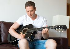 Man compose a song. Handsome man compose a song on the guitar Stock Images