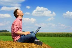 Handsome man with computer. Man working outside sitting on a haystack Stock Photos