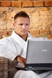 Handsome man with computer in bathrobe Stock Photos