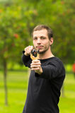 Handsome man concentrated aiming  a slingshot at Stock Images