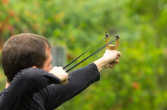 Handsome man concentrated aiming  a slingshot at Royalty Free Stock Images