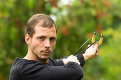 Handsome man concentrated aiming  a slingshot at Royalty Free Stock Photography