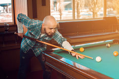 Handsome man concentrating on the game on the pool table Royalty Free Stock Photo