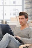 Handsome man concentrating on laptop screen. Handsome man concentrating on laptop computer screen, looking troubled, sitting in living room Royalty Free Stock Image