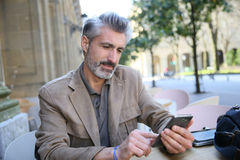 Handsome man connected on wifi with smartphone Stock Images