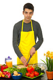 Handsome man cooking. Handsome man with yellow apron cooking  home against white background Royalty Free Stock Image