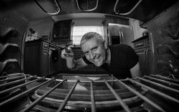 Handsome man cooking. Fish eye view of a handsome middle age man looking inside an oven in a home kitchen in black and white Stock Images