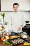 Handsome man cooking  fish  in baking sheet Stock Image