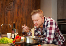 Handsome man cooking at home preparing pasta Royalty Free Stock Photography
