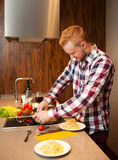 Handsome man cooking at home preparing pasta Stock Image