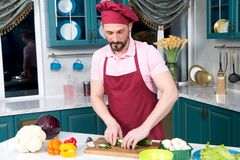 Guy holds cut zucchini in hands before steaming. A Handsome man cooking at home preparing vegan salad in kitchen. royalty free stock photos