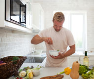 Handsome man cooking at home preparing salad in kitchen Stock Images