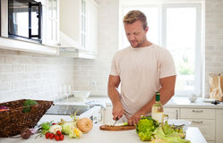 Handsome man cooking at home preparing salad in kitchen Stock Photos