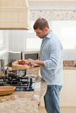 Handsome man cooking in the kitchen Stock Photo