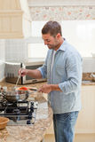 Handsome man cooking in the kitchen Stock Images