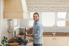 Handsome man cooking in the kitchen Stock Photography