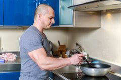 Handsome man cooking in the kitchen Royalty Free Stock Photos