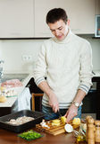 Handsome man cooking meat with  mushrooms and potatoes Stock Photography