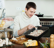 Handsome man cooking  meat with  mushrooms Stock Images